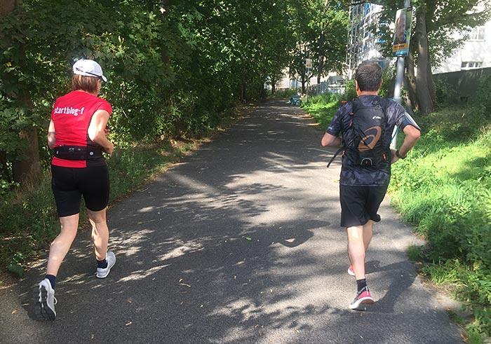 Läuferin und Läufer auf einem Parkweg