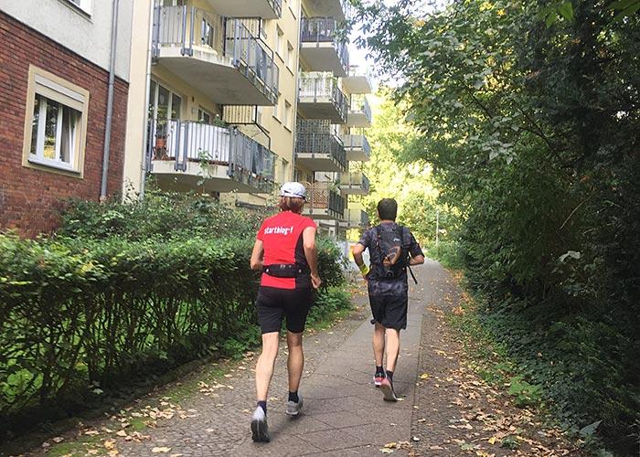 Läuferin und Läufer auf Fußweg neben einem Wohnhaus