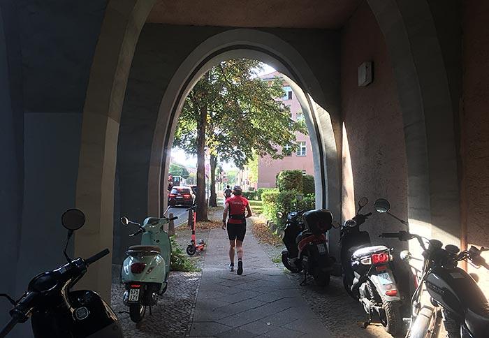 Läuferin in einem großen Torbogen, neben dem Weg stehen viele Motorroller