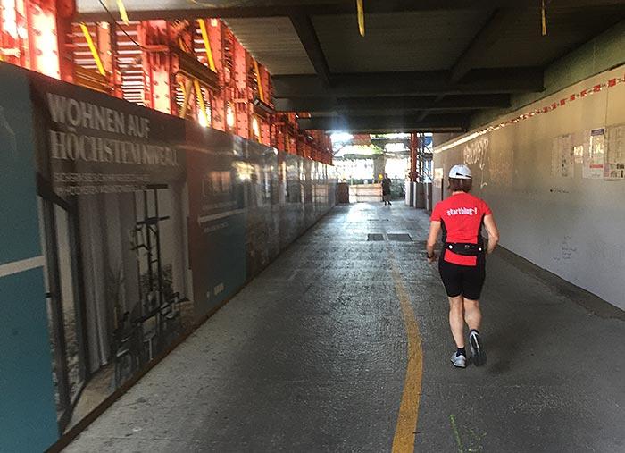 Läuferin in einer breiten, überdachten Baustellenpassage