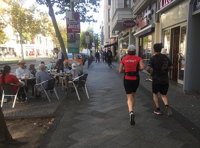 Läuferin und Läufer auf Fußweg, an dem auch Leute an den Tischen einer Bäckerei sitzen