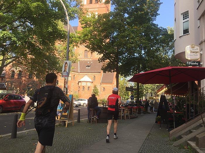 Läuferin und Läufer kurz vor einem Restaurant mit Außenbereich, im Hintergrund eine Kirche