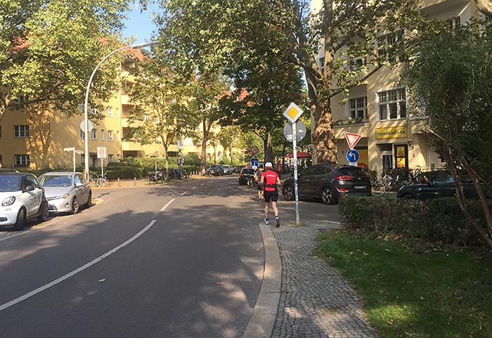 Läuferin auf einer gewundenen Straße mit vielen Bäumen