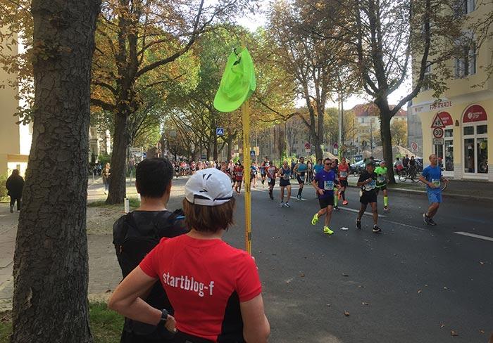Läuferfeld und Zuschauer mit neonfarbener Mütze am hochgereckten Zollstock