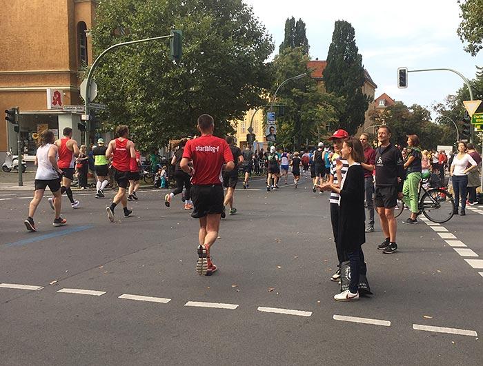 Marathonläufer:innen und Zuschauer:innen am Straßenrand