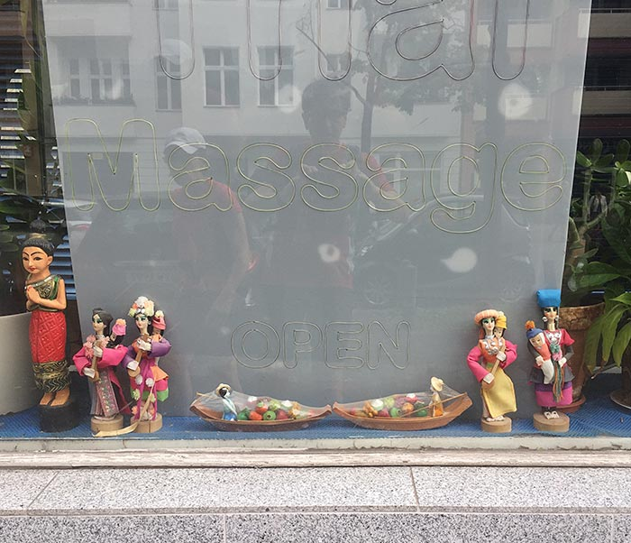 Asiatische Figuren im Schaufenster eines Thai-Massage-Ladens