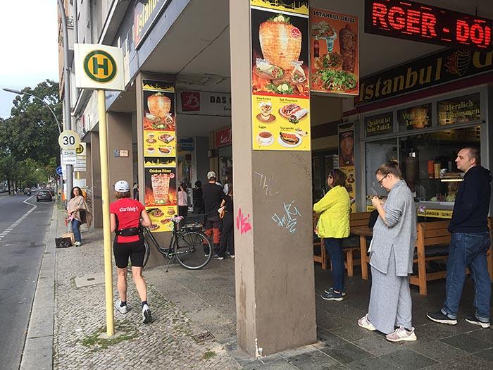 Läuferin läuft an Istanbul-Grill vorbei, neben dem Menschen in einer Schlange auf die Berlinwahl in ihrem Wahllokal warten