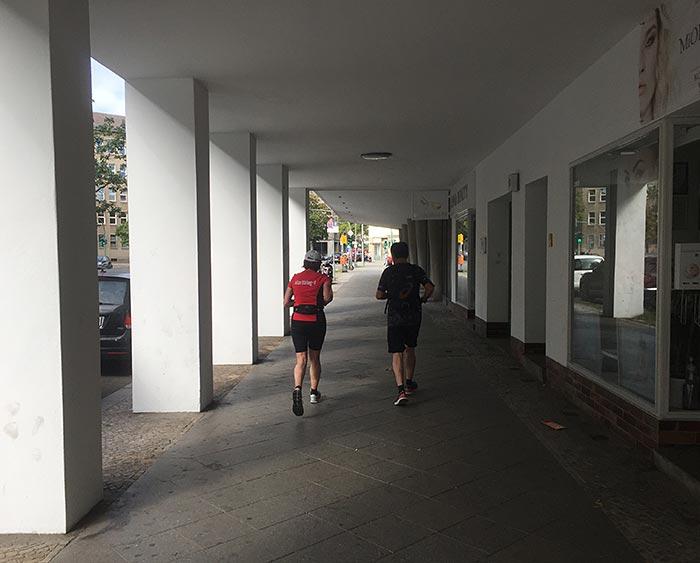Läuferin und Läufer in einer Säulenpassage