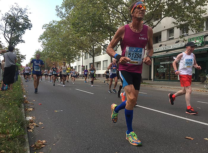 Hagerer Läufer mit glänzender Sonnenbrille und bunten Laufschuhen