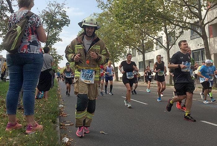 Lächelnder Marathonläufer im Feuerwehr-Anzug und Helm