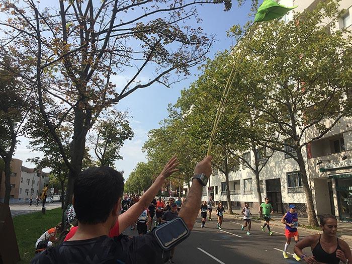 Läufer hält neonfarbene Mütze an Zollstock hoch
