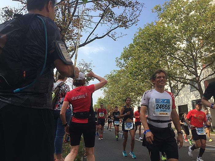Zuschauerin winkt entgegenkommendem Läufer zu