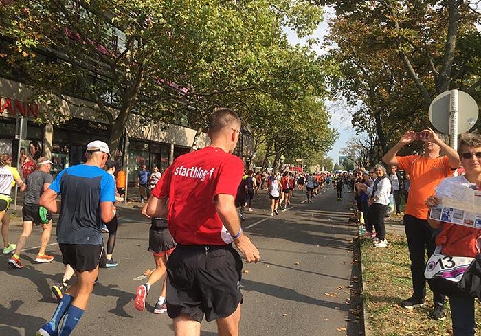 """Läufer mit rotem Shirt """"startblog-f"""" läuft weiter im Feld"""