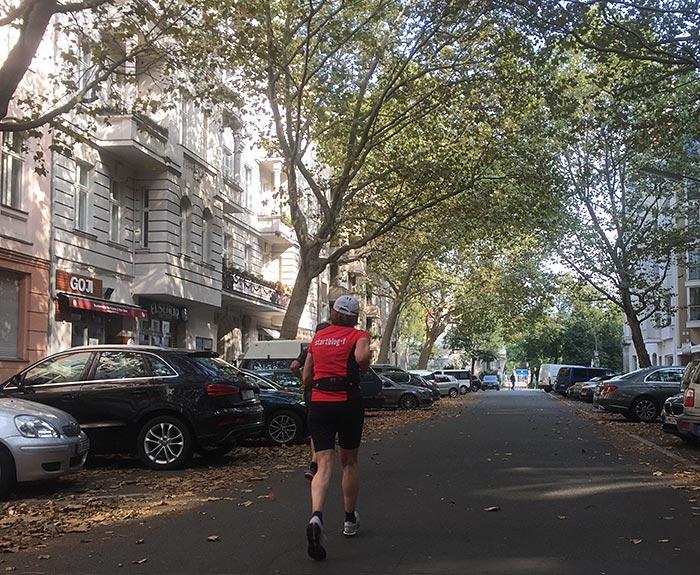 Läuferin auf von Bäumen überdachter Straße