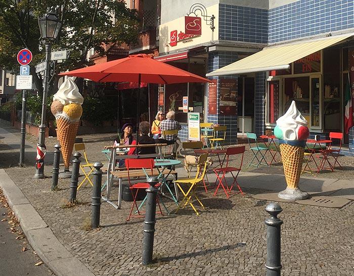 Bunte Stühle und Tische vor einem Eiscafé, daneben zwei große Werbe-Kunststoff-Eistüten