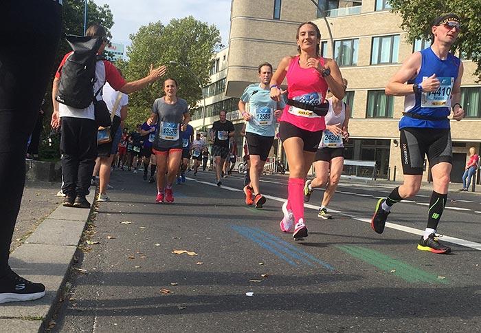 Läuferin in pinkem Shirt und pinken Strümpfen lächelt im Vorbeilaufen