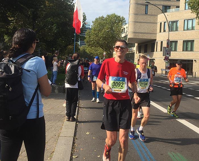 Läufer in rotem Shirt und Sonnenbrille lächelt