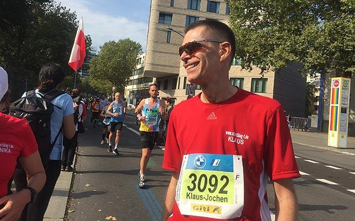 Läufer in rotem Shirt und Sonnenbrille steht und lacht