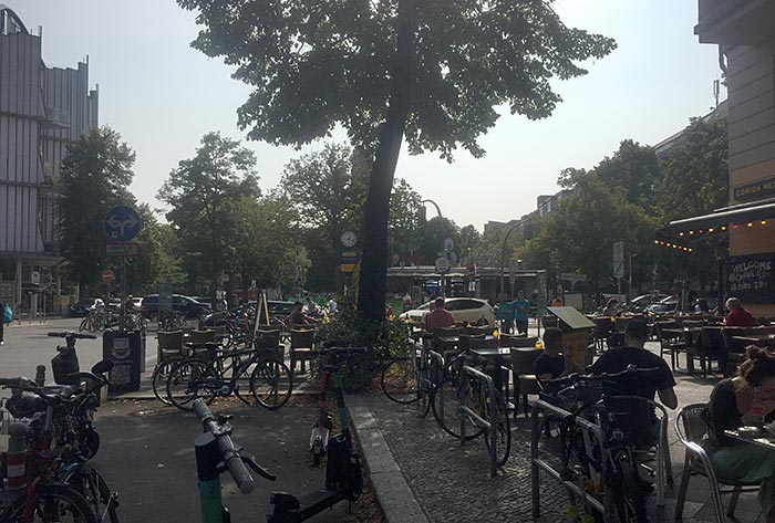 Blick auf den Winterfeldplatz, viele abgestellte Fahrräder und sitzende Leute in der Außengastronomie