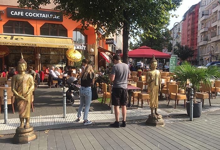 Asiatisches Café, davor zwei goldene Statuen und eine große Palme im Topf