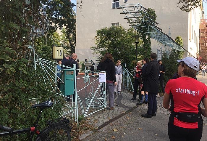 Wartende Wähler:innen vor einem modernvoll geformten Metallzaun des Architekten Baller