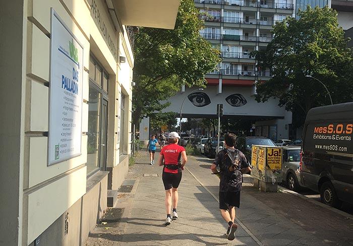Läuferin und Läufer vor einem Hochhaus auf dem die Illustration von zwei riesige Augen angebracht ist