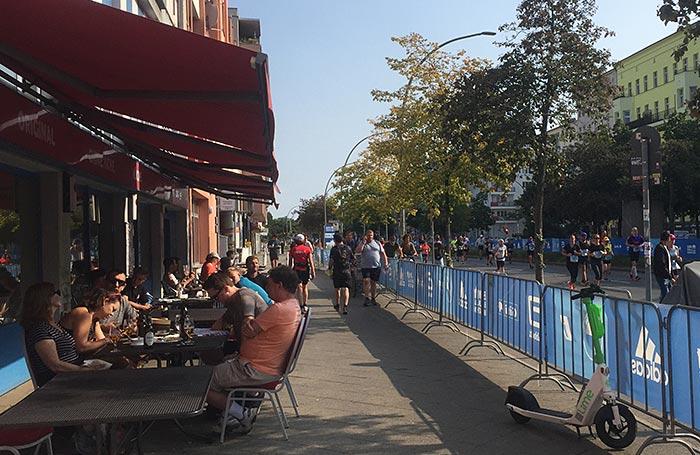 Leute sitzen im Café am Rand der Strecke, die hier mit einem blauen Banner abgesperrt ist