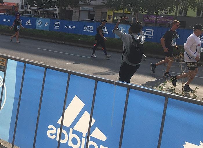 Jubelnde Zuschauerin feuert die letzten Läufer:innen an
