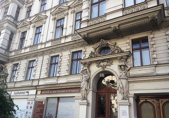 Historisches Gebäude mit Statuen am Portal und Zierfriesen