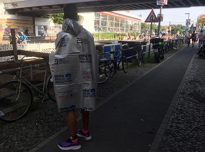 Läufer in silbernem Umhang des Berlin-Marathons sieht am Streckenrand auf die noch laufenden Teilnehmer:innen