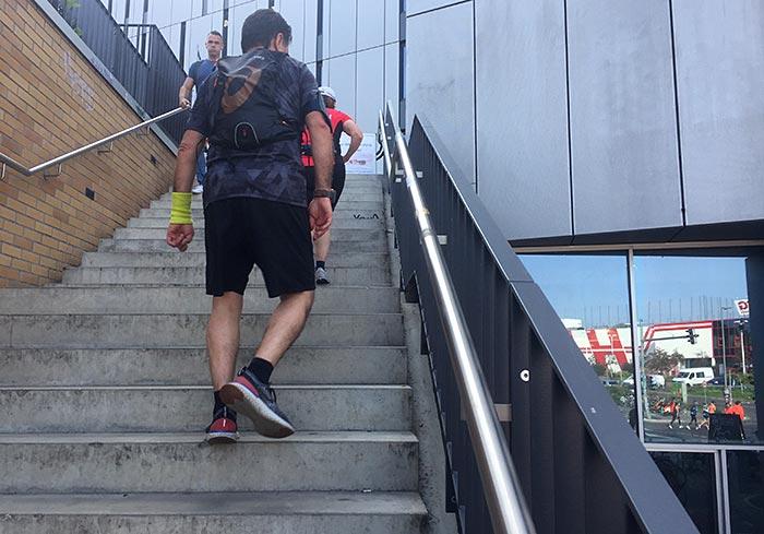 Läufer geht Treppen hoch, im spiegelnden Fenster des modernen Cafés daneben sieht man Marathon-Läufer:innen