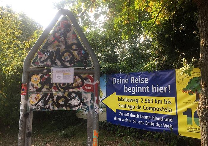 """Mit Grafitti völlig übersätes Schild einer Parkanlage, daneben ein Banner """"Deine Reise beginnt hier! Jakobsweg"""""""