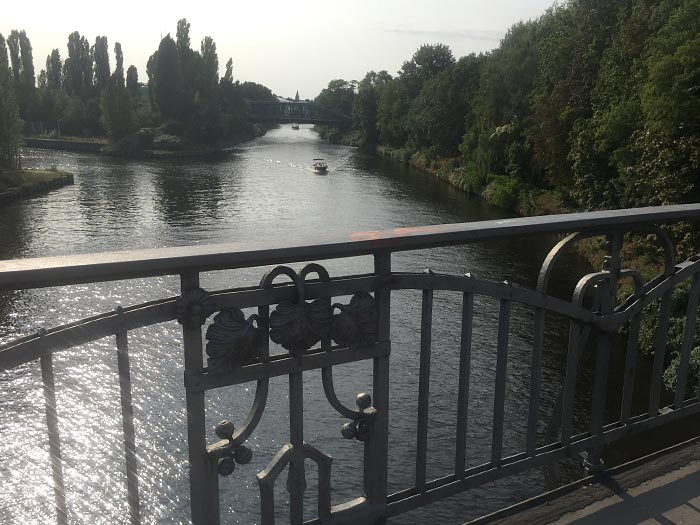 Blick von einer Brücke mit kunstvollem schmiedeeisernen Geländer auf den Kanal, auf dem ein Motorboot kommt