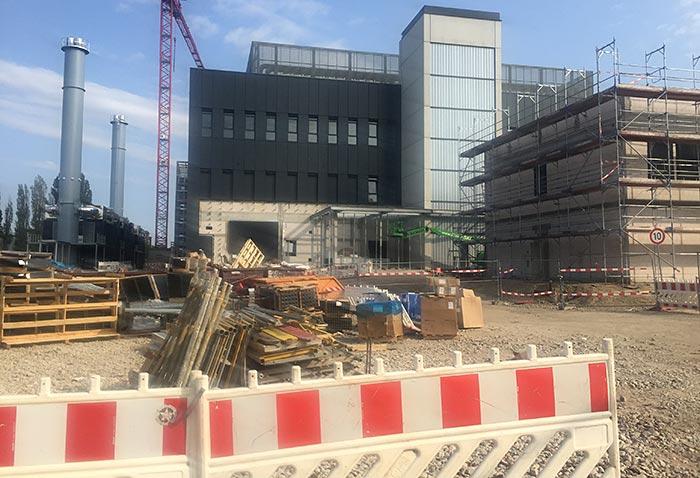 Rot-weißer Bauzaun vor der Baustelle eines modernen Gebäudes