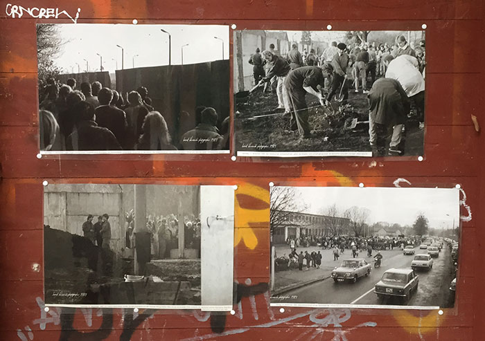 Historische Schwarzweiß-Fotos von der Berliner Mauer, angepinnt auf einer graffitibeschmierten Holztafel