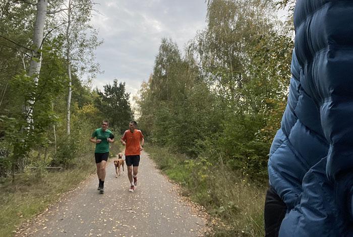 2 Läufer und 2 Hunde auf schmalem asphaltiertem Weg zwischen Bäumen und Büschen