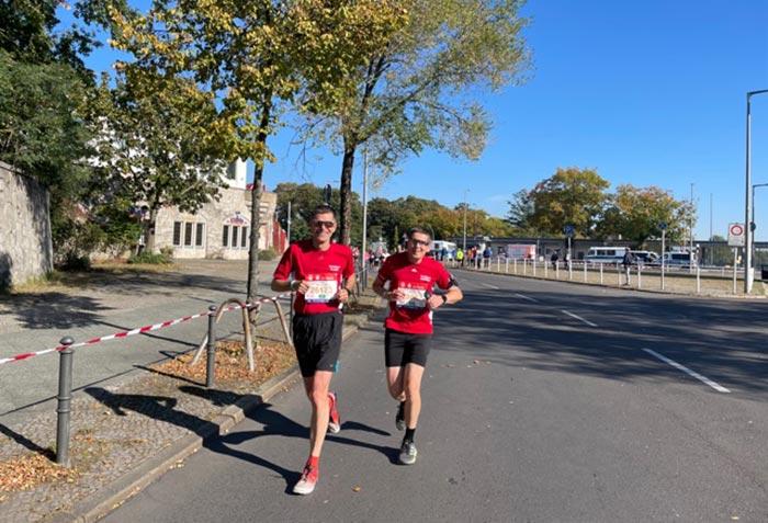 Zwei lächelnde startblog-f-Läufer in roten Shirts