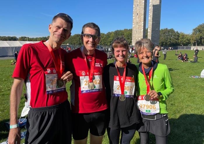 Lächelnde Laufgruppe mit Medaillen auf dem Außengelände des Stadions