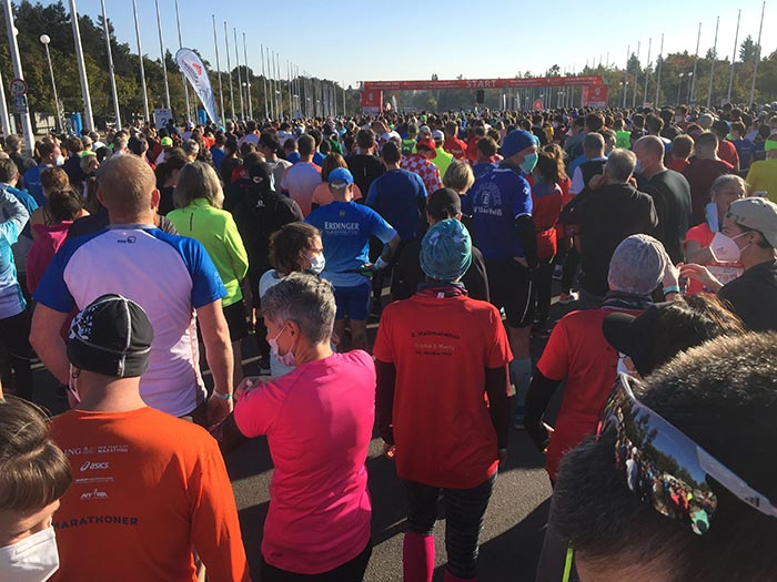Läuferinnen und Läufer im Startblock mit Blick auf den Startbogen