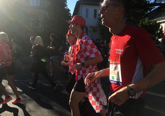 startblog-f-Läufer neben zwei Läufern mit rotem Hut und rot-weiß karierten langen Jacken