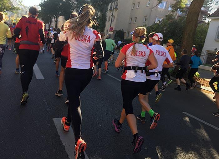 Zwei Läuferinnen und ein Läufer mit weißen Trikots mit Aufschrift Polska
