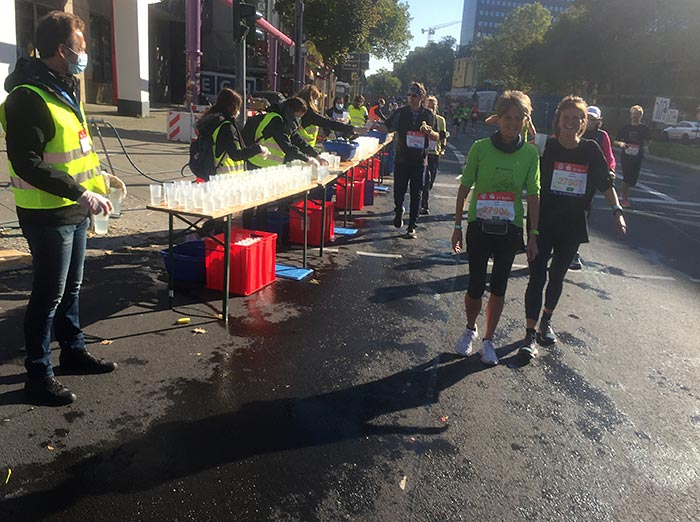 Lächelnde Läuferinnen am Getränkestand