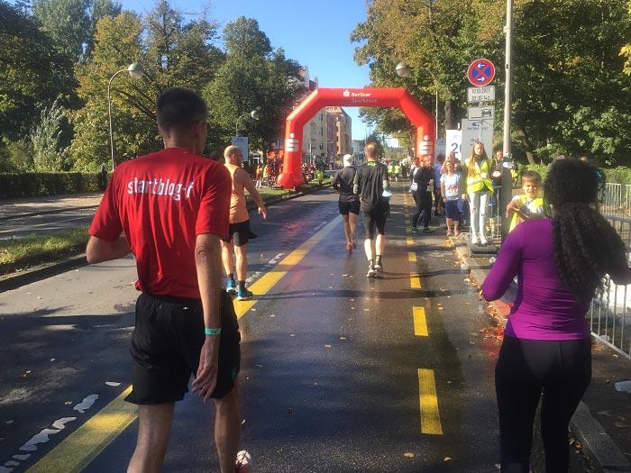 Läuferinnen und Läufer an einem Getränkestand auf der Neuen Kantstraße