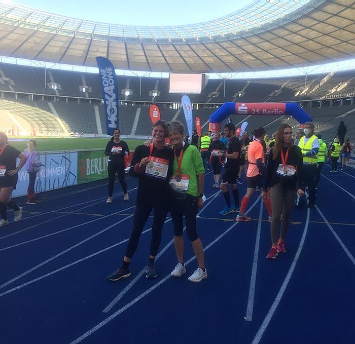 Glückliche Läuferinnen mit Medaillen im Zielbereich