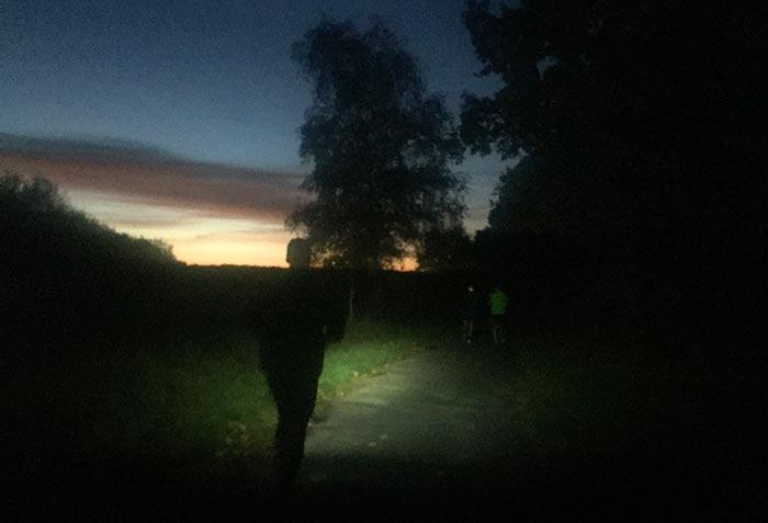 Läufer mit Stirnlampenlicht in schwarzer Landschaft, am Horizont ein leuchtender Sonnenaufgang